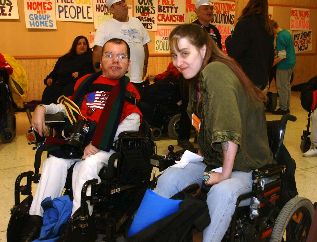 Man and Woman in front, seated in wheelchairs, smiling, people in background